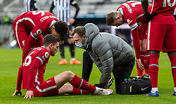 NEWCASTLE-UPON-TYNE, ENGLAND - Wednesday, December 30, 2020: Liverpool's Andy Robertson receives treatment for an injury to his left ankle during the FA Premier League match between Newcastle United FC and Liverpool FC at St. James' Park. The game ended in a goal-less draw. (Pic by David Rawcliffe/Propaganda)