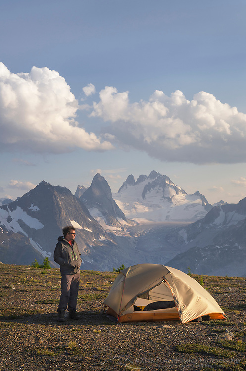 Adult male backpacker standing beside tent at backcountry camp on Rocky Point Ridge. Howser Towers Vowell Glacier in the distance. Bugaboo Provincial Park Purcell Mountains British Columbia.