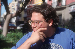 Portrait of teenage boy sitting outside looking thoughtful,