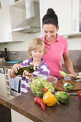 Woman with her son preparing salad in kitchen, Bavaria, Germany