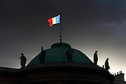 The Tricolore (French Flag) backlit by late afternoon sunlight on top of the Palais de Légion d'Honneur building in Paris