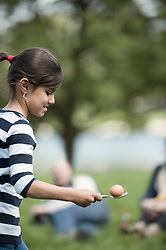 Girl balancing one egg on a spoon in park, Munich, Bavaria, Germany