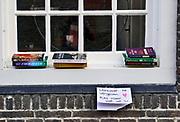 Nederland, Nijmegen, 29-3-2020  Bij een huis in de binnenstad liggen boeken in het raam buiten . Ze mogen gratis meegenomen worden . In deze tijd dat mensen binnen moeten blijven vanwege de coronacrisis lezen mensen mee. Foto: Flip Franssen