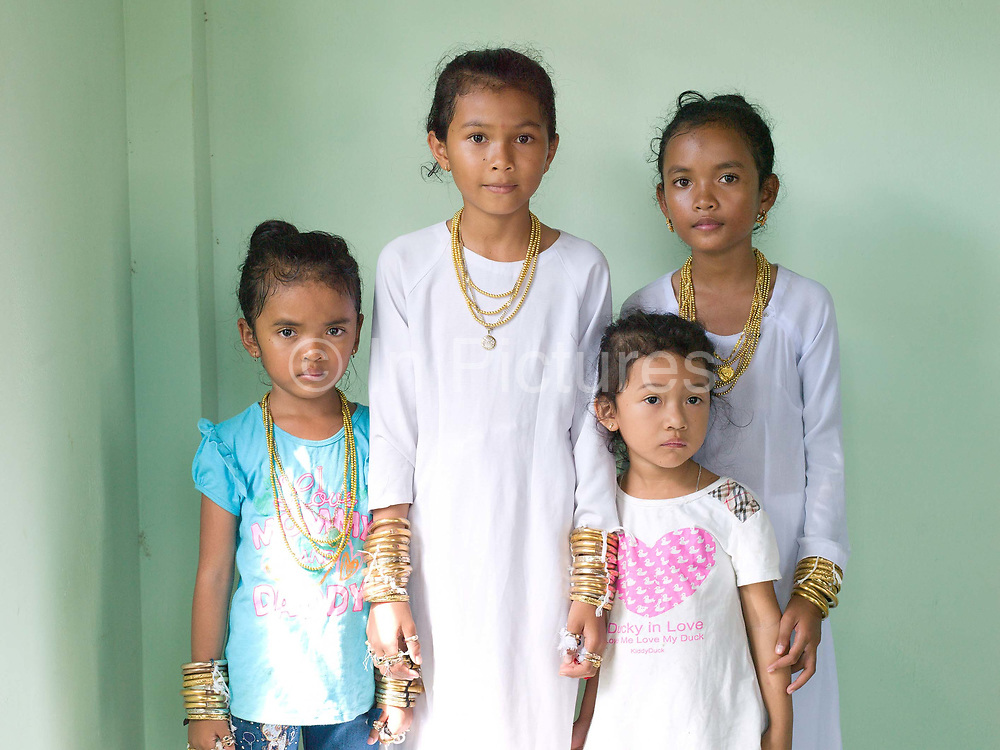 Portrait of Muslim Cham girls with their sisters at a Karoh (maturity) ceremony in Van Lam, Ninh Thuan province, Central Vietnam. Cham girls usually in groups of around 5, undergo a Karoh (maturity) ceremony, one of the most important ritual events of their lives and if it has not taken place, the girl cannot marry. The Cham, a Muslim community of around 39,000 people living along the coast of Central Vietnam are one of the 54 ethnic groups recognised by the Vietnamese government.