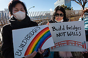Two Japanese women hold signs saying, Build Bridges not Walls at a protest march and rally organised by the Alliance for an Inclusive America group against the perceived anti-Muslim and anti-foreigner immigration policies of President Donald Trump, Shibuya, Tokyo, Japan. Sunday February 12th 2017. The Alliance of an Inclusive America is a multi-faith non-partisan group. About 250 Americans, other ex-pats and japanese people took part in the march to show people around the world they reject the Executive Order President Trump enacted at the end of January, indefinitely suspending the resettlement of Syrian refugees and temporarily banning people from seven majority Muslim countries from entering the United States.
