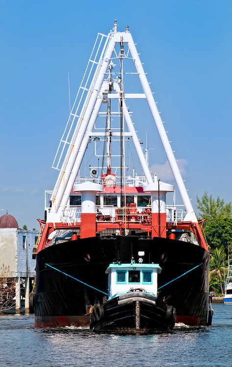 Tugboat guiding cargo ship in the Miami River.