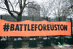 London, UK. 31 January, 2021. A 'Battle for Euston' banner hung by anti-HS2 activists from umbrella campaign group HS2 Rebellion from fencing erected by HS2 Ltd around Euston Square Gardens. Climbers from the National Eviction Team (NET) are currently dismantling a camp built by activists, five of whom still occupying tunnels beneath the camp, in order to seek to protect trees from felling by HS2 Ltd in connection with the controversial HS2 high-speed rail project.
