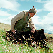 Gamekeeper Niel Pearson takes a rest from lifting turf from the moor for turfing shooting butts for the Middlesmoor grouse shoot, Upper Nidderdale, North Yorkshire, UK