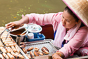 "10 JULY 2011 - DAMNOEN SADUAK, RATCHABURI, THAILAND:  A vendor in the floating market in Damnoen Saduak, Thailand, grills bananas on her boat. The Thai countryside south of Bangkok is crisscrossed with canals, some large enough to accommodate small commercial boats and small barges, some barely large enough for a small canoe. People who live near the canals use them for everything from domestic water to transportation and fishing. Some, like the canals in Amphawa and nearby Damnoensaduak (also spelled Damnoen Saduak) in Rajburi  province (also spelled Ratchaburi) are also relatively famous for their ""floating markets"" where vendors set up their canoes and boats as floating shops.     PHOTO BY JACK KURTZ"