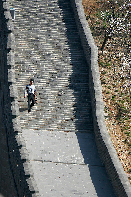One man walks along the top of the Badaling section of The Great Wall in China.  Badaling is the most visited section of The Great Wall.