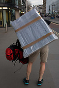 A man walks through the City of London carrying a bubble-wrapped flatscreen TV on his back. Striding across the capital at great speed, we see them from the rear with the item taped to his body - parcel tape keeping the valuable equipment in place. The load is both heavy and awkward and he occasionally stops to adjust the weight before continuing. Passers-by turn their heads at the comical activity - it's not every day one sees a man with a television on his back.