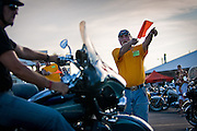 """Dan Wiltse of Spokane points a motorcycle rider in the right direction for parking outside the Cruiser's Drive-Thru Bar in Stateline on Thursday. This year marked the 6th annual Cruiser's Mini-Sturgis, which is affectionately known as the """"Woodstock of motorcycle rallies."""""""