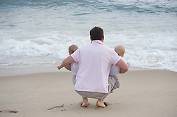 back of a man holding two babies by the ocean