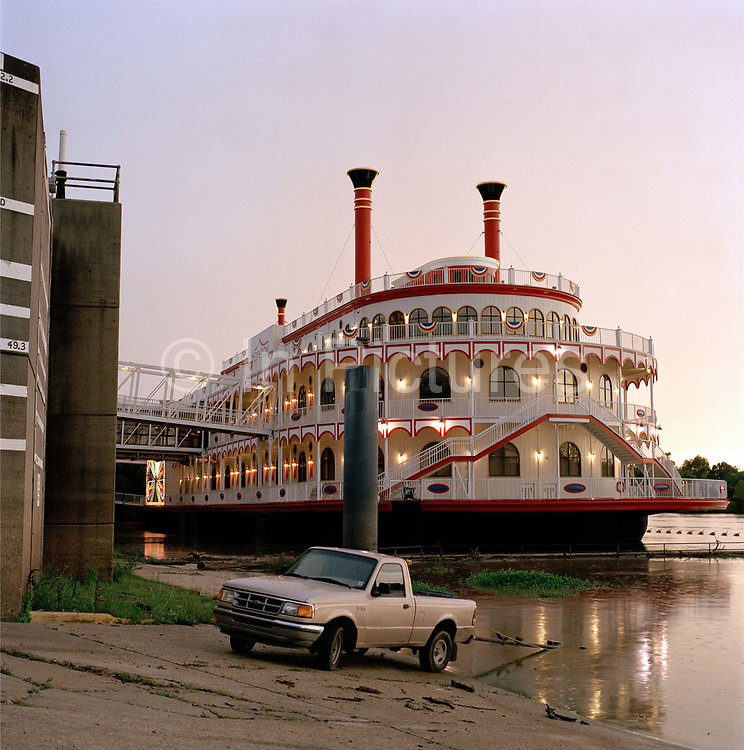 """Casino on converted steamer, Vicksburg, Mississippi at dusk. This elegant historic town with its pillar fronted houses and cotton legacy  is transformed as the remains of a storm at sunset  turn the sky iridescent. There are perhaps defining moments on all big trips. Arriving in Vicksburg, Mississippi at dusk just as a  huge thunderstorm was beginning to break was one of them . <br /> <br /> <br /> """"It had been raining so hard, that an alligator had mistook the<br /> four-lane Interstate for the swollen Mississippi beside it and tragically met its death there. But as we drew into elegant Vicksburg, with its pillar-fronted houses on hilly streets, something astonishing happened.<br /> The sky, the result of a hot, setting sun, and the remains of a storm, was suddenly alive with an iridescent glow, so otherworldly, it looked like a space ship had landed.  A rainbow stretched between two red brick towers, and you could just hear hear a steamer's horn, as it edged its way down the mighty Mississippi"""