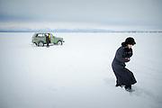 A couple returning from ice fishing, Lake Baikal. Siberia, Russia