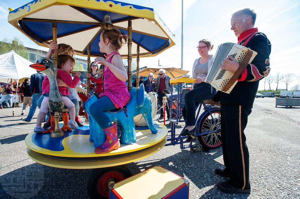 Een vrouw drijft door de trappen op de bakfiets de draaimolen voor de kinderen aan. In Nijmegen vindt voor de vierde keer het internationale bakfietstreffen aan. Tijdens het tweedaags evenement wisselen bedrijven en bakfietsers ervaringen uit. Bakfietsen worden in heel Europa steeds vaker ingezet, zowel door particulieren als bedrijven. Het is een duurzame vorm van transport en biedt veel voordelen.<br /> <br /> In Nijmegen for the third time the International Cargo Bike Festival is hold. The two-day event focuses on the use and users of cargobikes. Cargo bikes are increasingly being deployed across Europe, both individuals and businesses. It is a sustainable form of transport and offers many advantages.