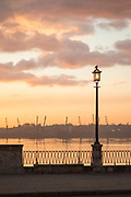View of bay and sidewalk with street lamp at sunset, Havana, Cuba
