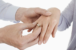 Man placing ring on woman's finger, Bavaria, Germany