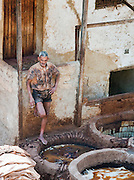 A man takes a short break at the Tannery in the medina, where men dye leathers to colour and preserve them, Fes, Morocco