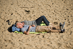 © Licensed to London News Pictures. 28/03/2012..Saltburn, England..As temperatures rise this week the beach at Saltburn in Cleveland attracts the visitors as they enjoy the warm weather. A couple doze in the morning sunshine...Photo credit : Ian Forsyth/LNP