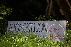 Wendover, UK. 16th June, 2021. A painted sign criticising the cost of the HS2 high-speed rail link is pictured outside Stop HS2's Wendover Active Resistance Camp alongside the A413. Large areas of land around Wendover in the Chilterns AONB have already been cleared of trees and vegetation for the rail infrastructure project in spite of concerted opposition from local residents and environmental activists.