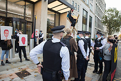London, UK. 10 November, 2020. Metropolitan Police officers speak to environmental activists from Extinction Rebellion standing outside the Shell Centre to mark the 25th anniversary of the killings of the Ogoni Nine. The Ogoni Nine, leaders of the Movement for the Survival of the Ogoni People (MOSOP), were executed by the Nigerian government in 1995 after having led a series of peaceful marches involving an estimated 300,000 Ogoni people against the environmental degradation of the land and waters of Ogoniland by Shell and to demand both a share of oil revenue and greater political autonomy.