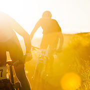 Two mountain bikers with white number plates race on a cross-country course late in the evening.