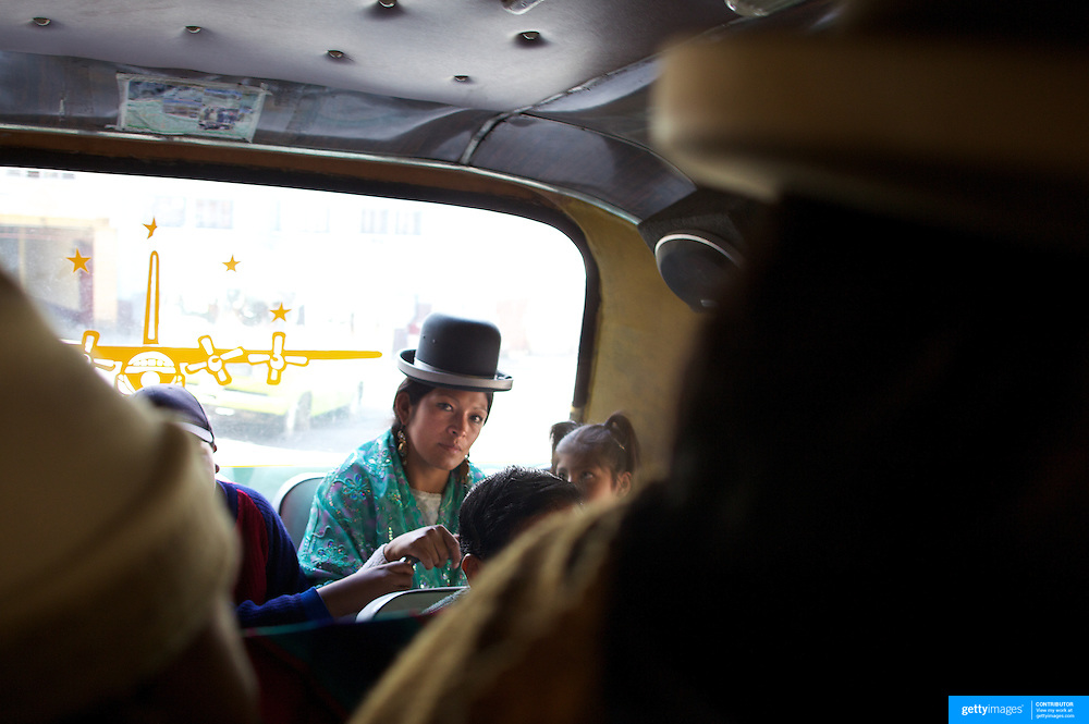 Cholita wrestler Yolanda La Amorosa  travels home on a bus with her daughter Adriana after collecting her from school in La Paz, Bolivia. Yolanda is part of the 'Titans of the Ring' wrestling group who perform every  Sunday at El Alto's Multifunctional Centre. Bolivia. The wrestling group includes the fighting Cholitas, a group of Indigenous Female Lucha Libra wrestlers who fight the men as well as each other for just a few dollars appearance money. El Alto, Bolivia, 17th March 2010. Photo Tim Clayton