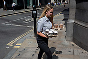 A young woman carries trays of coffees and iced drinks during the 2018 heatwave in the City of London, the capitals historic financial district, on 2nd August 2018, in London, England.