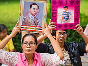 13 OCTOBER 2016 - BANGKOK, THAILAND:  Women hold up portraits of Bhumibol Adulyadej, the King of Thailand, while they pray for him at Siriraj Hospital. Thousands of people came to the hospital to pray for the beloved monarch. Bhumibol Adulyadej, the King of Thailand, died at Siriraj Hospital in Bangkok Thursday, October 13, 2016. Bhumibol Adulyadej, 5 December 1927 – 13 October 2016, was the ninth monarch of Thailand from the Chakri Dynasty and is known as Rama IX. He became King on June 9, 1946 and served as King of Thailand for 70 years, 126 days. He was, at the time of his death, the world's longest-serving head of state and the longest-reigning monarch in Thai history.      PHOTO BY JACK KURTZ