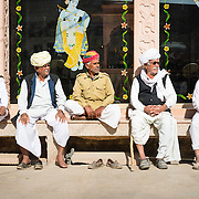 Group of men sitting outside a Hindu temple in an Indian village
