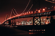 Oakland-San Francisco Bay Bridge photographed from Yerba Buena Island. City lights of San Francisco seen in the background. Time exposure of car lights.