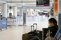 Edinburgh, Scotland, UK. 27 March, 2020. Interior views of a deserted Edinburgh Airport during the coronavirus pandemic. With very few flights during the current Covid-19 crisis passengers are scarce in the terminal building. Solitary passenger wearing a face mask in the terminal building.  Iain Masterton/Alamy Live News