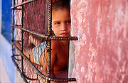 23 JULY 2002 - TRINIDAD, SANCTI SPIRITUS, CUBA: A boy in the window of his home in the colonial city of Trinidad, province of Sancti Spiritus, Cuba, July 23, 2002. Trinidad is one of the oldest cities in Cuba and was founded in 1514. Homes in Trinidad are not air conditioned and are frequently left open to allow Carribbean breezes to blow through them. .PHOTO BY JACK KURTZ