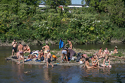 © Licensed to London News Pictures. 25/06/2020. London, UK. Members of public are seen relaxing and swimming by the canal at Hackney Wick, east London. Key to easing the lockdown in England will be the two-meter rule - the distance people should stay apart to stop catching coronavirus. Record temperatures are expected this week as the UK starts to relax lockdown restrictions, introduced earlier this year to prevent the spread of COVID-19.<br /> Photo credit: Marcin Nowak/LNP