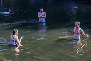 People swim and enjoy taking a selfie in the River Lea in east London on Friday, Aug 7, 2020, as the UK could see record-breaking temperatures with forecasters predicting Friday as the hottest day of the year. (VXP Photo/ Vudi Xhymshiti)