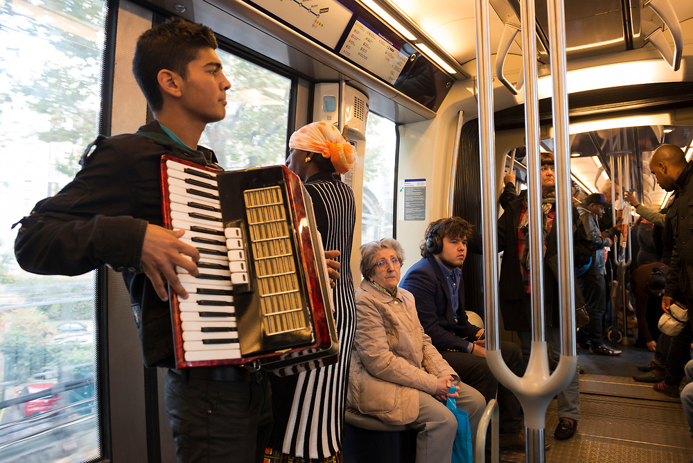 A young man plays the accordian on a metro car in Paris, France