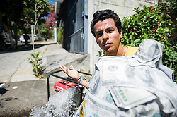 A student from the Central American University (UCA) poses for a picture next to a water pipe used by a company to clean a sewer system. Hundreds marched on international water day to the Salvadoran Sugar Industry Headquarters to protest against lobbying for a bill that would privatize water services.