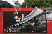 Art work by kennardphillipps at Shangri-la at the Glastonbury Festival 22th July 2016, Somerset, United Kingdom. Figures of refugees sit above a bilboard with part Sky News and desperate refugees. Shangri-la is a venue at the festival with  art and politics mixed with tunes and all night club nights. Work getting the festival ready takes weeks and in the days up to the festival starts work is frantic.  The Glastonbury Festival runs over 3 days and has 3000 acts, including music, art and performance and approx. 150.000 attend the anual event.