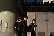 Four high school boys walk under the  Shuto expressway overpass in a park in Edogawabashi, Tokyo, Japan Friday April 20th 2018