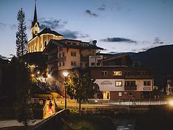 THEMENBILD - eine Frau spaziert über einen beleuchteten Steg zur Kirche, aufgenommen am 07. August 2020 in Kaprun, Österreich // a woman walks across an illuminated footbridge to the church, Kaprun, Austria on 2020/08/07. EXPA Pictures © 2020, PhotoCredit: EXPA/ JFK