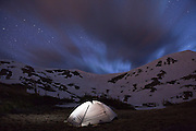 Clouds streak through the night sky over an illuminated tent at Parika Lake, Never Summer Wilderness, Colorado.