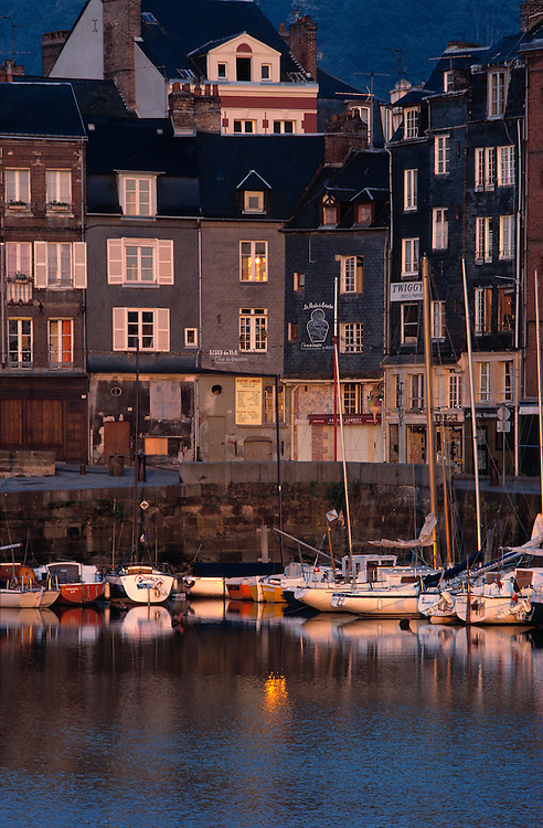 Dusk light shades the harbor at Honfleur in Normandy, France.