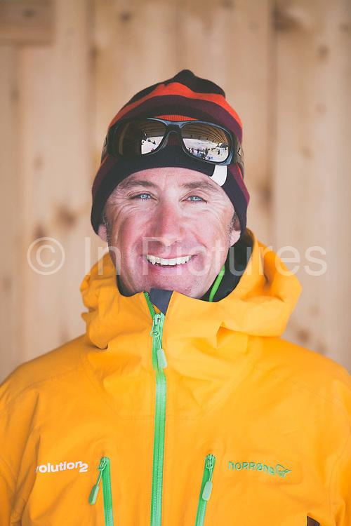 Head and shoulder portrait of a male skier outside a traditional woodedn chalet, Refuge De Bostan, in Vallée de la Manche in Morzine / Portes du Soleil ski area on 22nd March 2017 in France