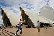 Tourists take photographs outsideSydney Opera House, Australia