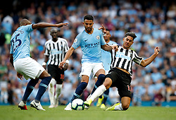 Manchester City's Riyad Mahrez (centre) and Fernandinho (left) battle for the ball with Newcastle United's Ayoze Perez (right) during the Premier League match at the Etihad Stadium, Manchester.