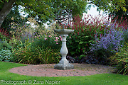 Armillary Sun Dial in front of autumn border with Perovskia 'Blue Spire' and Persicaria affinis 'Superba' RHS AGM, Rosa - pink rose possibly 'The Fairy'?, seed heads of Phlomis russeliana, background:  Stipa gigantea, and Verbena bonariensis - September