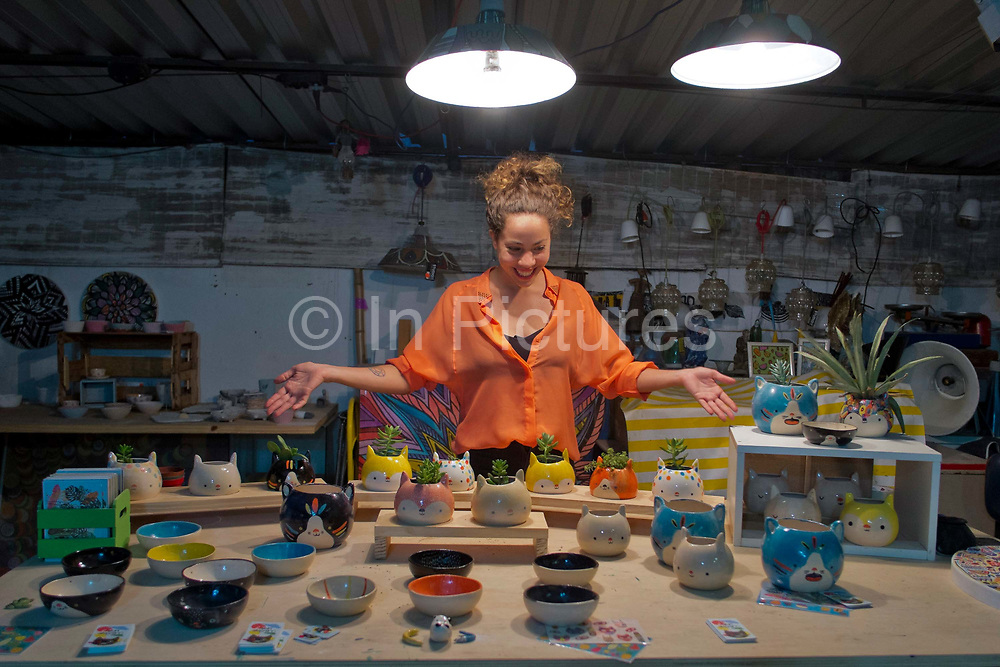 Artist in her atelier in Santa Teresa, showing her pots for sale at an open studios in the bohemian neighbourhood, known for astisans, Rio de Janeiro.