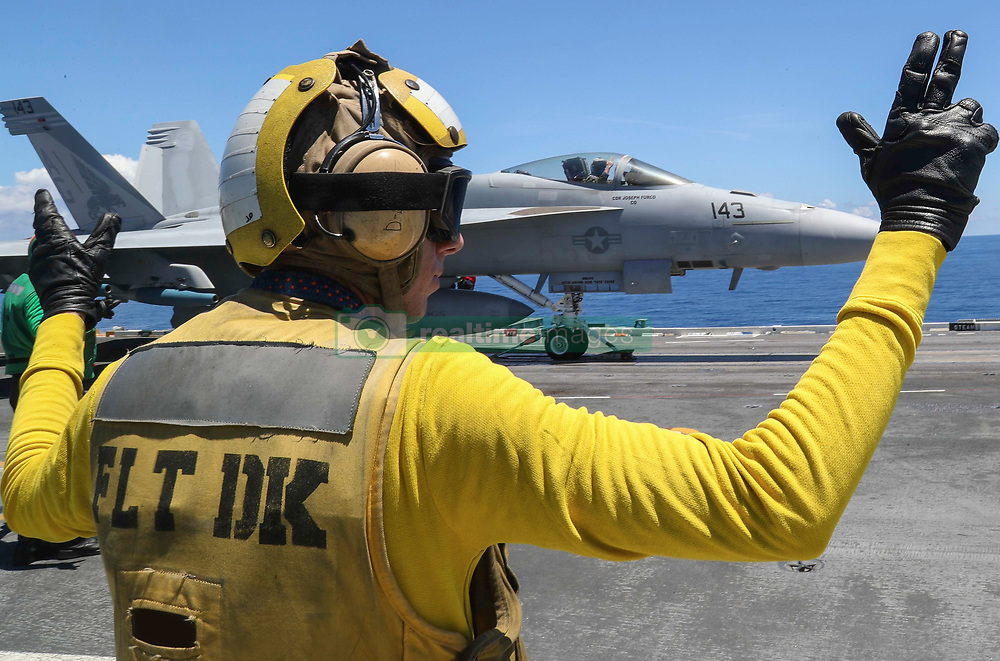 """ATLANTIC OCEAN (Aug. 7, 2018) Aviation Boatswain's Mate (Handling) 1st Class Jeremy Parrish directs an F/A-18F Super Hornet assigned to the """"Pukin' Dogs"""" of Strike Fighter Squadron (VFA) 143 on the flight deck of the Nimitz-class aircraft carrier USS Abraham Lincoln (CVN 72). (U.S. Navy photo by Mass Communication Specialist 3rd Class Shane Bryan/Released)180807-N-AD724-0002"""