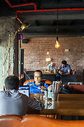 People working and socialising at the Hauz Khas Social, a unique restaurant and cafe and office space in Hauz Khas Village, New Delhi, India